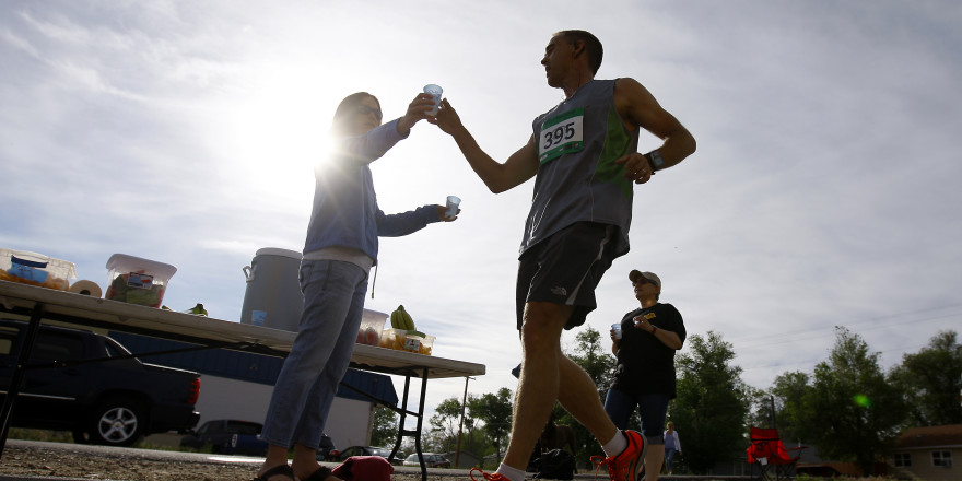 Wyoming Medical Center's Paula Mongold hands out water to runners participating in the half marathon section of the Casper Marathon on June 2, 2013, in Casper, Wyo. (Dan Cepeda)