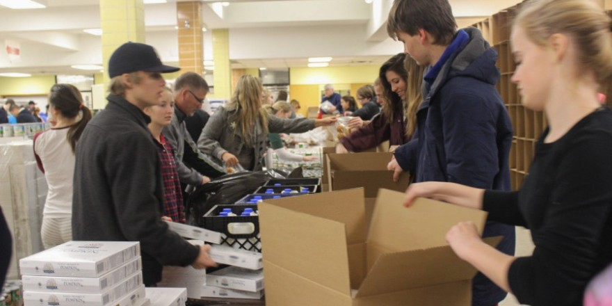 freshman-ashley-jallen-pulls-a-box-down-the-assembly-line-to-be-filled-with-food-items-900x600